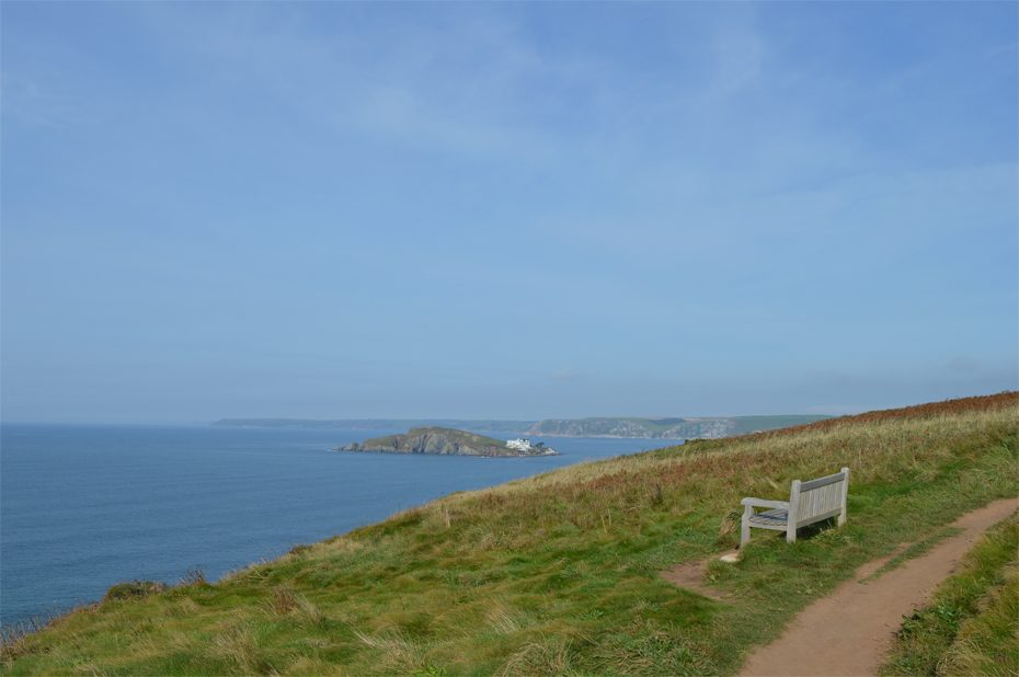 A bench on the coast path with views of Burgh Island
