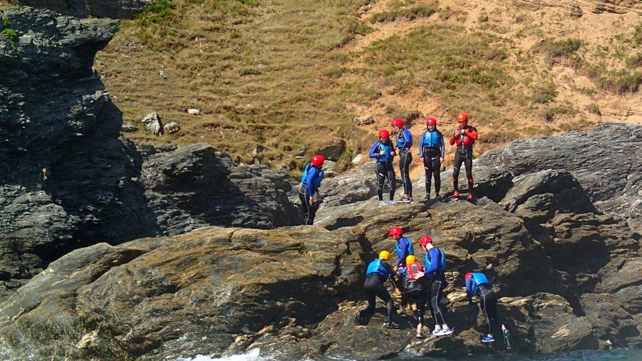A group taking part in coasteering by Gara Rock in South Devon