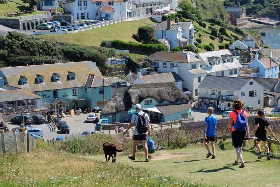 A family walks downhill from the South West Coast Path into Hope Cove